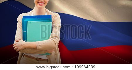 Teacher with files against digitally generated russian national flag