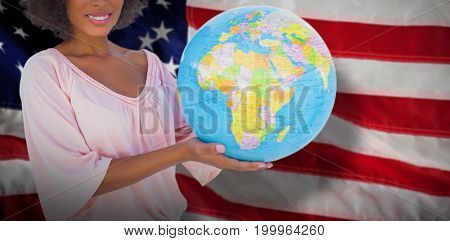Smiling woman holding globe against close-up of an flag
