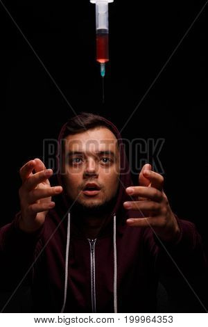 A handsome young man leaning towards syringe with antibiotics. Sick guy in a red hoodie stretches out his hands towards drugs on a black background. Professional treatment and healthcare concept.