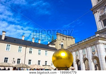 Salzburg, Austria - May 01, 2017: The golden ball statue with a man on the top sculpture, Kapitelplatz Square, Salzburg, Austria on May 01, 2017.