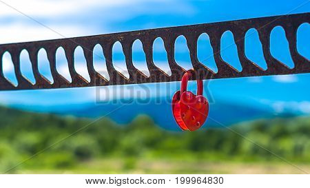 A single heart shaped red padlock symbolizing love hanging on the bridge handrails with blurred river greenery mountains and blue sky in background