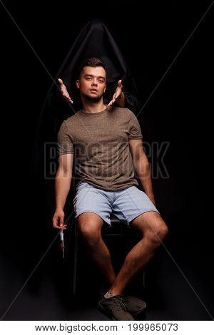 A mentally ill young man in casual clothes sitting on a chair on a black background. Suicidal guy and death, stretching hands towards him. Problematic, anxious male suffering from self-loathing.