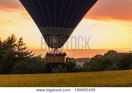 Saxon Germany - August 13 2017. Hot air balloon landing at field and people in the basket fly over the landscape in Saxon. Germany
