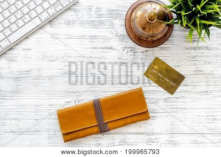 Book hotel online. Bank card and purse near service bell and keyboard on light wooden table background top view.