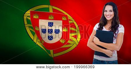 Happy student with notepad against digitally generated portugese national flag