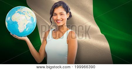 Pretty woman showing globe against digitally generated nigerian national flag