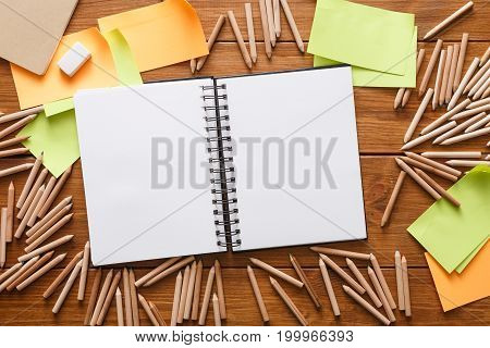 Top view of office table with stationery. Open sketchbook, color pencils and blank sticky notes to remember all ideas at wooden background, copy space, nobody, objects