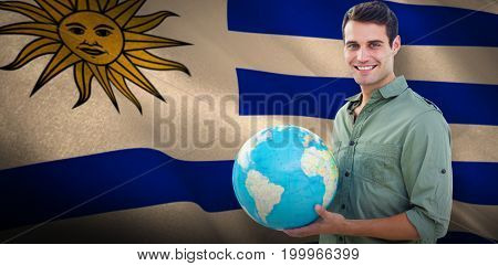 Happy man with globe against digitally generated uruguay national flag