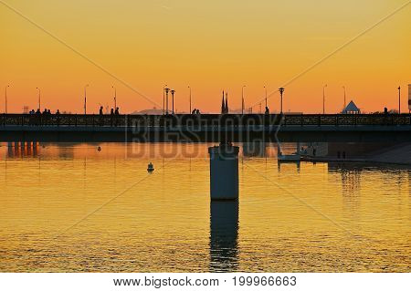 View to the Astana city and pedestrian bridge over the Ishim river at dusk in Astana, Kazakhstan.