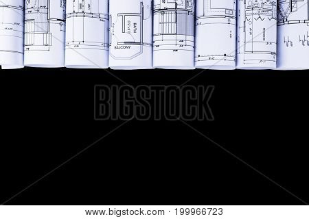 Architectural blueprints and blueprint rolls and a drawing instruments on the white worktable background. Drawing compass plans.Construction background.