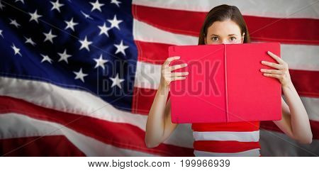 Student holding book over face against close-up of an flag