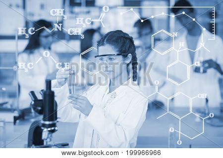 Digital image of chemical formulas against attentive schoolgirl doing a chemical experiment in laboratory