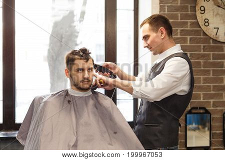 Barber make haircut with trimmer hair clipper in barbershop. Hairstyle in barbershop.