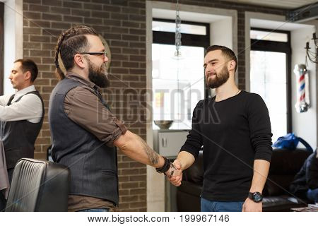 Thankful client and barber shaking hands after haircut. Hairstylist and satisfied customer handshaking at barbershop