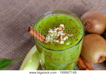 Close-up of a blended drink from ripe kiwi and lime with grated almonds and cinnamon sticks on a light brown fabric background. A few whole juicy kiwi, lime cut in half and a slice of apple on a desk.