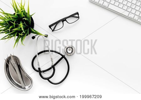 An appointment. Doctor's workplace in clinic. Stethoscope near keyboard on white background top view.