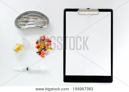 Doctor's table. Clip pad, pills, syringe and cuvette with ampoulie on white background top view.