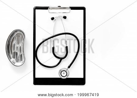 Doctor's table. Clip pad, stethoscope and cuvette with ampoulie on white background top view.