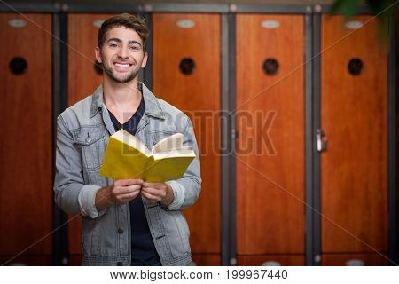Student smiling at camera in library against close-up of brown lockers