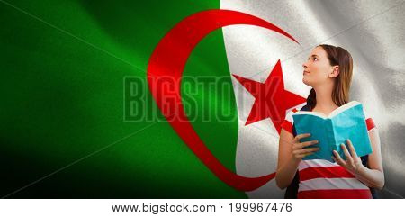 Student reading book in library against digitally generated algerian national flag