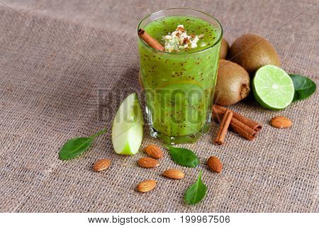 A view from above of a heap of a natural kiwi and lime cut in half on a light brown fabric background. A healthful smoothie from tropical fruits and grated almonds on a table. Copy space.