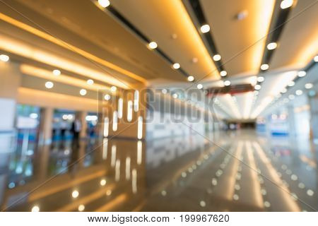 Blurred defocused bokeh background of grand hallway exhibition hall or trade show event. International convention center modern interior architecture or commercial tradeshow organizer concept
