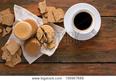 Norwegian homemade brown cheese brunost with crackers and cup of coffee on wooden desk, top view