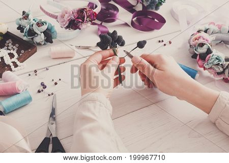Master making handmade jewelry, woman pov. Needlewoman workplace with plastic beads, flowers and tools for creating accessories