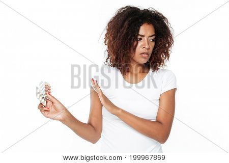 Picture of sad young african lady standing isolated over white background. Looking aside holding pills.