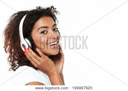 Image of cheerful young african lady standing isolated over white background. Looking camera listening music in headphones.