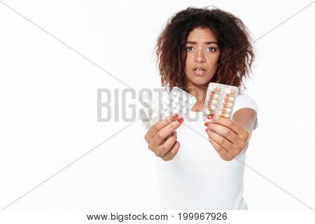 Picture of sad young african lady standing isolated over white background. Looking at camera holding pills.
