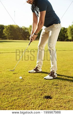 Cropped image of a male golfer about to tee off a golf ball at the green course