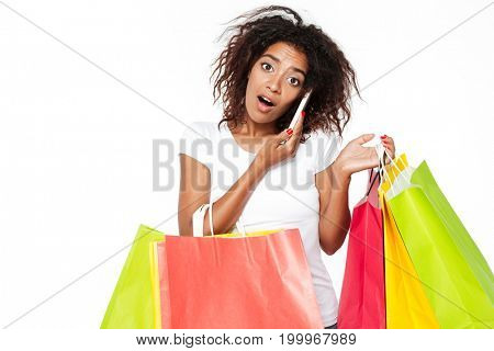 Image of happy young african woman isolated over white background. Looking camera holding shopping bags talking by phone.