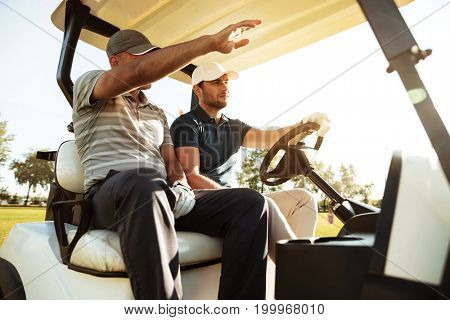 Two male golfers sitting in a cart