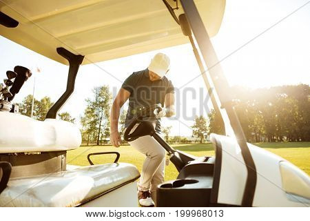 Young male golfer getting in a golf cart