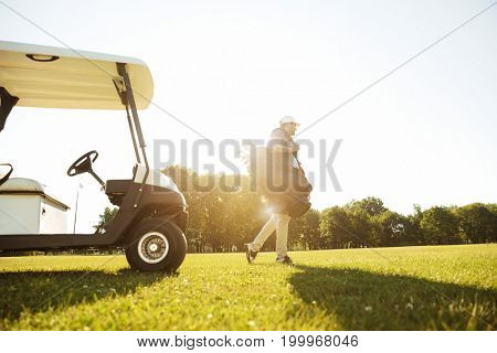Male golfer walking with golf bag along green course