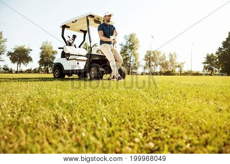 Young man resting while leaning on a golf cart and holding golf club