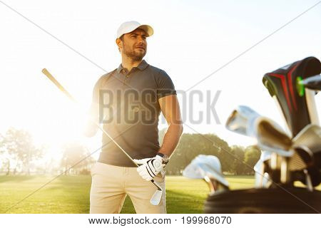 Young man carrying golf club while standing on a sunny green field