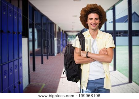 Young man with arms crossed in office corridor against empty corridor at school