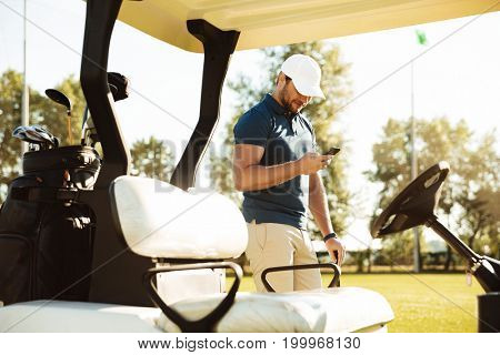 Young man using mobile phone while standing at a golf cart on a field