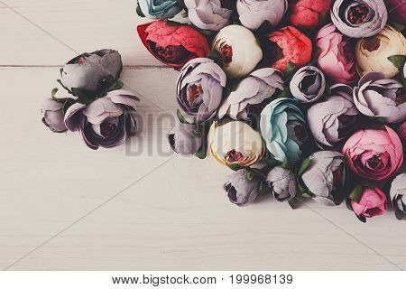 Beautiful artificial flowers variety, copy space. Lots of handmade fabric blossom on light wooden table, floristic and handicraft background.