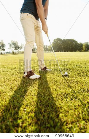 Cropped image of a golfer putting golf ball on green outdoors