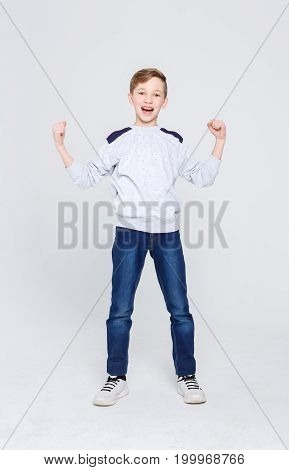 Full length portrait of cheerful boy celebrating victory over white studio background. Happy smiling boy with braces posing on camera. Positive lifestyle and health care concept. Vertical, copy space