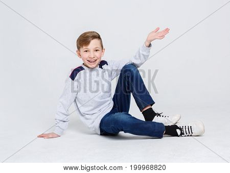 Portrait of happy smiling boy in braces sitting on the floor at white studio background. Kid in casual clothes posing on camera, copy space