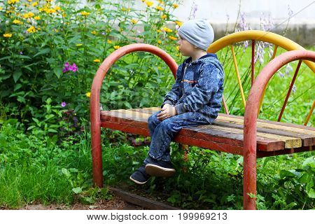 Little Boy Sitting On A Bench In A Park And Sad