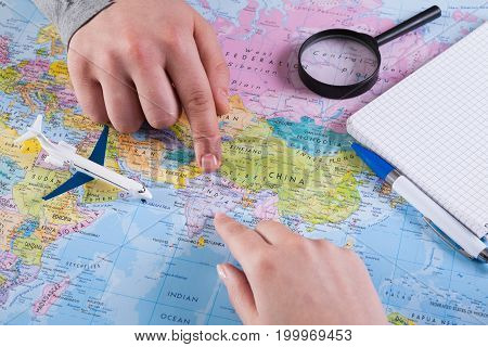 Couple planning airplane trip to India, point on map, taking notes in blank notebook, copy space