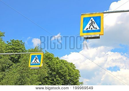 Road signs pedestrian crossing on background of trees
