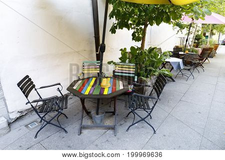 Colorful outdoor cafe tables and chairs near yellow wall
