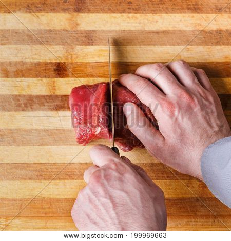 Man cutting filet mignon in pieces. Chef preparing fresh meat for cooking on wooden board at restaurant kitchen. Modern cuisine backgroung with copy space, top view