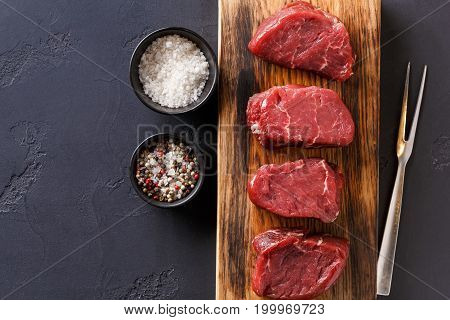 Raw filet mignon steaks with spices closeup. Slices of fresh beef arranged in a row on wooden cutting board, spices and meat fork at black slate background, top view, copy space